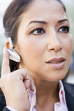 Woman using bluetooth earpiece. Outside Royalty Free Stock Photography