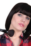 Woman using blusher brush Stock Images