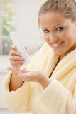Woman using body lotion. Young woman wearing bathrobe, using body lotion, smiling Stock Images
