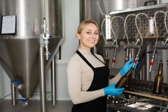 Woman using bottling equipment on brewery Stock Images