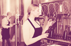 Woman using bottling equipment on brewery Stock Photography