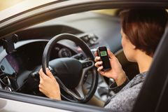 Woman using breath alcohol analyzer in the car. Young millennial woman using breath alcohol analyzer in the car. Closeup with selective focus. Girl taking royalty free stock image