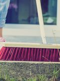 Woman using broom to clean up backyard patio stock afbeeldingen