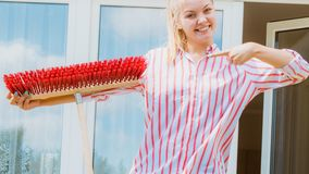 Woman using broom to clean up backyard patio stock foto