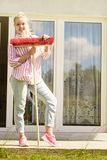 Woman using broom to clean up backyard patio royalty-vrije stock fotografie