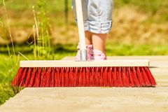 Woman using broom to clean up backyard patio royalty-vrije stock foto