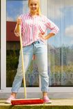 Woman using broom to clean up backyard patio. Female adult young woman using big broom to clean up backyard patio royalty free stock images