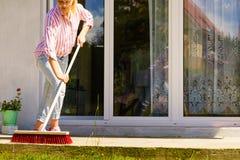 Woman using broom to clean up backyard patio. Female adult young woman using big broom to clean up backyard patio royalty free stock image