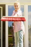 Woman using broom to clean up backyard patio royalty free stock image