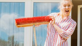 Woman using broom to clean up backyard patio stock photo