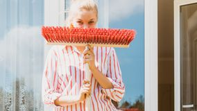 Woman using broom to clean up backyard patio. Female adult young woman using big broom to clean up backyard patio Stock Photography