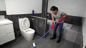 Woman using brush to cleaning the tile in bathroom. Woman using brush to cleaning the tile in the bathroom stock video footage