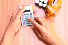 Woman using calculator and piggy bank and stack coins put beside stock image