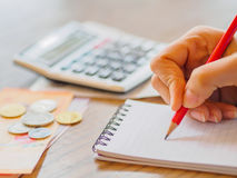 Woman using calculator. And thinking about cost on desk at home office Stock Photography