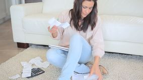 Woman using calculator. Video of woman using calculator while sitting on the floor stock video