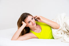 Woman using cell phone in bed Royalty Free Stock Photo