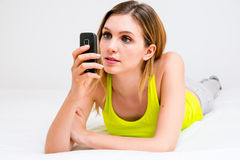 Woman using cell phone in bed Royalty Free Stock Images