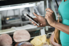 Woman Using Cell Phone In Cheese Shop Stock Images