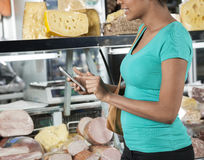 Woman Using Cell Phone In Cheese Shop Stock Photo