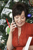 Woman Using Cell Phone By Christmas Tree Stock Photos