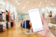 Woman using Cell phone in clothing store Stock Photo