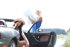 Woman using cell phone in convertible while friend reading map on road Royalty Free Stock Image