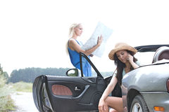 Woman using cell phone in convertible while friend reading map on road Royalty Free Stock Images