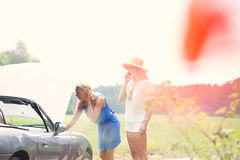 Woman using cell phone while friend examining broken down car Stock Photos