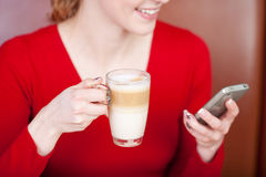 Woman Using Cell Phone While Holding Cafe Latte Cup Stock Image