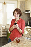 Woman using cell phone at home Stock Photo