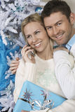 Woman using cell phone with man embracing her by Christmas tree Stock Image