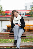 Woman Using Cell Phone On Park Bench Royalty Free Stock Photography