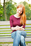 Woman Using Cell Phone in a Park Stock Images