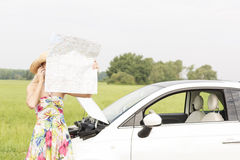 Woman using cell phone while reading map by broken down car at countryside Royalty Free Stock Photos