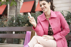 Woman Using Cell Phone Sitting on Bench Stock Image