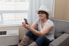 Woman using a cell phone wearing a cowboy hat. Woman wearing a cowboy hat sitting and using a cell phone Stock Photo