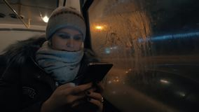 Woman using cell while traveling by bus in night city. Slow motion shot of a young woman traveling by bus in night winter city and using mobile to pass the time stock footage