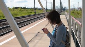 Woman using cell when waiting for commuter train on the platform. Young woman with backpack using cellphone while waiting for commuter train on the platform in stock video footage