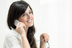 Woman using cellphone. Brunette woman using a white cellphone and smiling Royalty Free Stock Photo