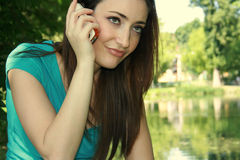 Woman using cellphone. A portrait of a young woman listening to a disappointing cellphone message while sitting outdoors in a park Royalty Free Stock Images