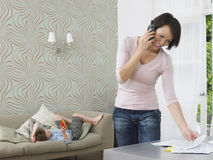 Woman Using Cellphone And Boy On Lying Couch Stock Photo