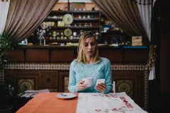 Woman using a cellphone in a cafe. Young woman drinking coffee in cafe and using phone. Young hipster girl texting with his mobile phone at the bar and having Royalty Free Stock Images