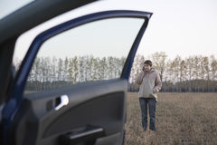 Woman Using Cellphone By Car In Field Stock Photos