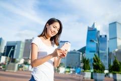 Woman using cellphone at city of Hong Kong Stock Image
