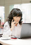 Woman using a cellphone and a computer Royalty Free Stock Image