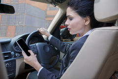 Woman using cellphone while driving car Royalty Free Stock Photo