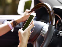 Woman using cellphone while driving. Hands of female holding cellphone and steering wheel inside a vehicle Stock Photo