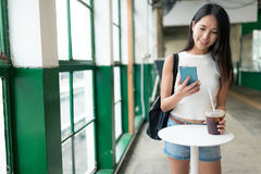 Woman using cellphone and enjoy her coffee in Hong Kong city Stock Photo