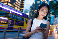 Woman using cellphone in Hong Kong city at night. Asian young woman Stock Photo