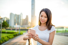 Woman using cellphone in Hong Kong city during sunset Royalty Free Stock Photography
